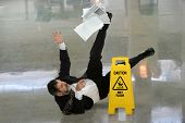 stock photo of wet  - Senior businessman falling on wet floor in front of caution sign - JPG