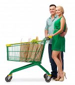 happiness, shopping and couple concept - smiling couple with shopping cart and food in it