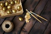 Golden Easter eggs in box with paintbrushes and thread on wooden background