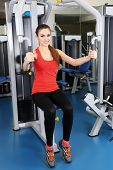 Beautiful woman training with weights in gym