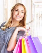 Closeup portrait of sweet cheerful girl standing in big shopping center with colorful paper bags, do