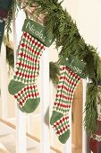 stock photo of bannister  - Two Christmas stockings with name Nicolas and Logan on stair bannister - JPG