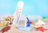 Thermometer  in sand on bright background
