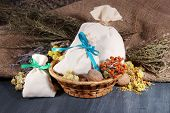 Textile sachet pouches with dried flowers, herbs and berries on wooden table, on sackcloth backgroun