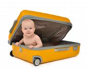 stock photo of infant  - Happy infant baby toddler sitting in yellow plastic travel suitcase on wheels getting ready for vacation isolated on a white background - JPG