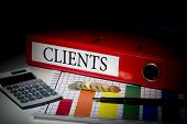The word clients on red business binder on a desk