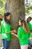 Group of multiethnic environmentalists standing around tree trunk in park