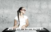Pretty school girl in funny glasses playing piano