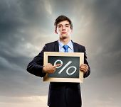 Handsome businessman holding frame with percentage symbol