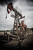 image of nonrenewable  - Oil rig pump dramaticly underexposed against contrast cloudy sky low angle view - JPG