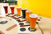 stock photo of porter  - beer flight of six sampling glasses of pilsner lager ale porter and stout craft beer - JPG