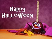 image of toffee  - Happy smiling crazy face red toffee apple candy for trick or treat Halloween food against a bright dark pink red and orange background with sample text - JPG