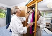 stock photo of dress-making  - Senior woman selecting clothes from closet at home - JPG