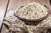stock photo of oats  - Portion of Oat in a bowl on vintage wooden background (close-up shot)