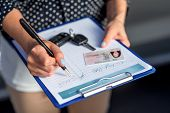 picture of rental agreement  - Young woman car rental inspector filling contract - JPG