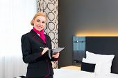 pic of housekeeper  - Housekeeping manager or assistant controlling hotel room or suit with checklist on tidiness  - JPG