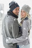 image of cold-shoulder  - Cute couple in warm clothing hugging smiling at camera against snow falling - JPG