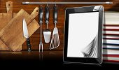 image of kitchen utensils  - Black tablet computer with blank pages in a kitchen on wooden wall with kitchen utensils - JPG