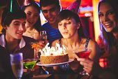 stock photo of blowing  - Pretty girl blowing on candles on birthday cake at party - JPG