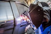 stock photo of manufacturing  - Man welding with reflection of sparks on visor - JPG