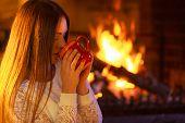 ������, ������: Girl Warming Up At Fireplace Holds Mug