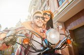 stock photo of vespa  - Beautiful young couple riding scooter together while happy woman bonding to her boyfriend and smiling - JPG