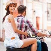 foto of scooter  - Rear view of beautiful young couple riding scooter together while beautiful woman looking over shoulder and smiling - JPG