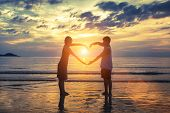 stock photo of romantic  - Silhouette of young romantic couple during tropical vacation - JPG