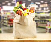 foto of supermarket  - Brown table and on background blured supermarket and bag with products - JPG