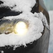 stock photo of headlight  - Car headlight flashing under the snow outdoor close up stock image - JPG