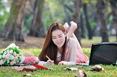 foto of wooden pallet  - woman sitting on wooden mat and writing notepad at parkland - JPG