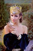 stock photo of queen crown  - Elegant young woman dressed like queen with a crown holding an apple - JPG