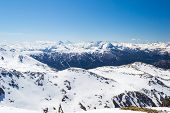 stock photo of torino  - Wide angle view of a ski resort in the distance with elegant mountain peaks arising from the alpine arc in late winter season and beginning of spring - JPG