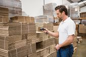 stock photo of warehouse  - Serious warehouse worker holding scanner in warehouse - JPG