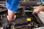 foto of garage  - Mechanic examining under hood of car at the repair garage - JPG