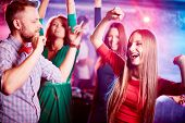 image of clubbing  - Happy young couple and their friends on background dancing together in night club - JPG