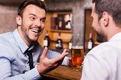 picture of gesture  - Two happy young men in shirt and tie talking to each other and gesturing while drinking beer at the bar counter - JPG
