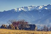 picture of haystack  - Peaceful rural mountain landscape with traditional Romanian mountainous farm with old wooden barn and haystacks in Moeciu Brasov county Trasylvania region Romania - JPG