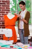 picture of foreground  - Beautiful young fashion designer adjusting dress on the mannequin and smiling with sewing machine on the foreground - JPG