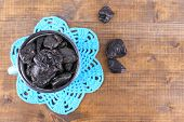 stock photo of doilies  - Cup filled with prunes on blue lace doily - JPG