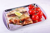 picture of pangasius  - Dish of Pangasius fillet with rosemary and lime on metal tray and color wooden table background - JPG
