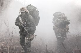 stock photo of raid  - Group of jagdkommando soldiers Austrian special forces in the smoke - JPG