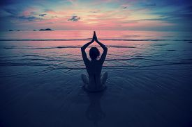 foto of sea life  - Silhouette young woman practicing yoga on the beach at surrealistic sunset - JPG