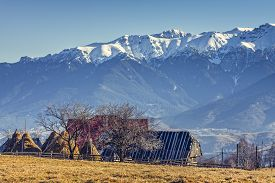 stock photo of haystacks  - Peaceful rural mountain landscape with traditional Romanian mountainous farm with old wooden barn and haystacks in Moeciu Brasov county Trasylvania region Romania - JPG
