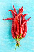 image of red hot chilli peppers  - Red hot chili peppers on blue wooden background top view - JPG