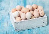picture of lunch box  - Farm fresh chicken eggs in box on blue wooden background - JPG