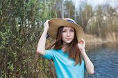 pic of windy  - Freckled girl in hat on the lake in windy day - JPG