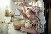 image of cake-mixer  - Mother and daughter spending quality time together in the kitchen preparing dough for homemade birthday cake - JPG