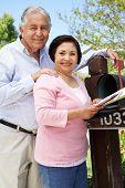 stock photo of mailbox  - Senior Hispanic Couple Checking Mailbox - JPG