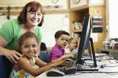 stock photo of middle class  - Elementary School Pupil With Teacher In Computer Class - JPG
